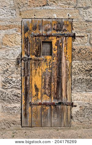 Old weathered yellow wooden door in stone wall