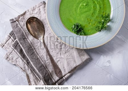 Vegetarian vegan broccoli cream soup served in blue plate with fresh parsley, broccoli, spoon, textile napkin over gray concrete background. Top view with copy space. Healthy eating.