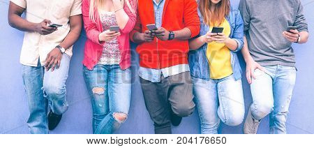 Teenagers texting mobile phone messages leaning on urban wall - Group of multiracial friends using cellular standing outdoors - Concept of students addiction to social network and telephone technology