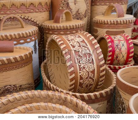 Handicrafts made of birch bark. Various wooden dishes toys and other utensils at a traditional russian fair.