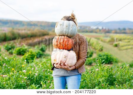 Beautiful young woman with three huge different pumpkins on a farm or patch. Girl having fun with farming. Thanksgiving or halloween. Harvesting time on autumn