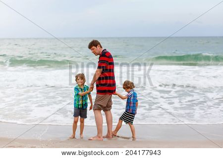 Two happy little kids boys and father standing on the beach of ocean and looking on horizon on stormy day. Family, dad and cute sons making vacations, dreaming and enjoying summer.