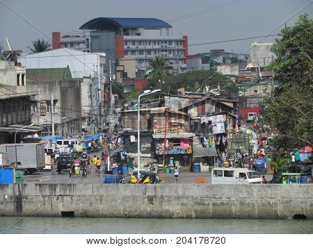 Manila Philippines, 10 February 2015: Street view in poor neighborhood in Manila with people walking in the street