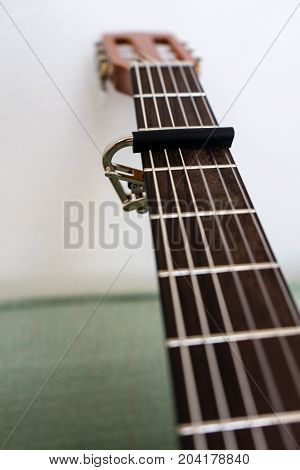 brown guitar neck with capo low angle view close up