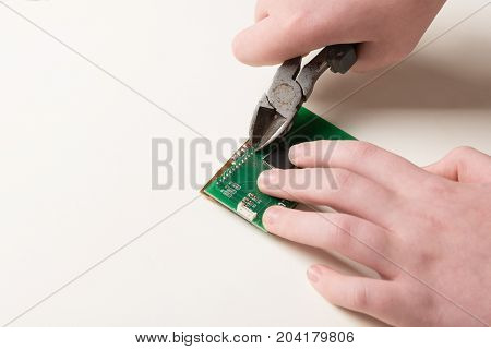 Microchip repair with pliers by human hands