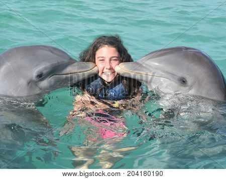 Happy Handsome Young Girl Laughing And Swimming With Dolphins In The Blue Swimming Pool On A Bright