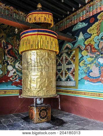 Wall paintings and large prayer wheel inside the portico of the Punakha Dzong dating from 1637 Punakha Bhutan Asia