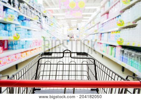 Shopping trolley in supermarket with blured supermarket aisle and shelves background.