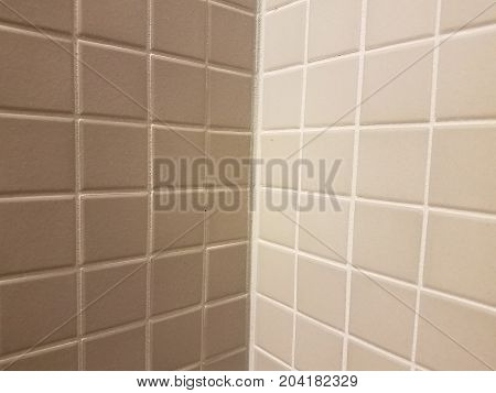 many square grey tiles on a bathroom wall