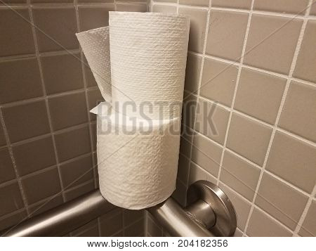 many square grey tiles on a bathroom wall and toilet paper