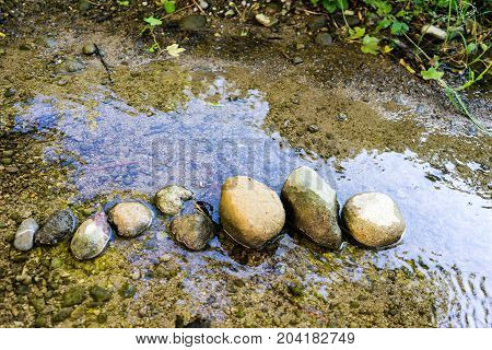 stones lined up in small creek with water reflection