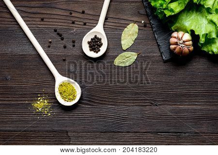 spices for cooking and fresh salad on wooden table top view