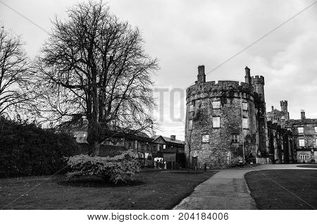 Kilkenny Ireland. Kilkenny Castle and gardens in autumn with heavy clouds. It is one of the most visited tourist sites in Ireland. Black and white