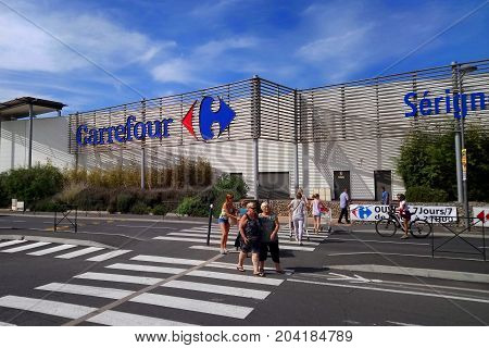 Serignan, France - August 20 2017: Shoppers Outside The Carrefour Supermarket In Serignan On A Sunny
