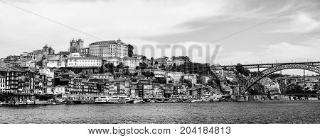 Porto Portugal. Panoramic view of colorful old houses of Porto Portugal with Luis I Bridge - a metal arch bridge over Douro River. It is a symbol of the city and a most popular touristic attraction. Black and white