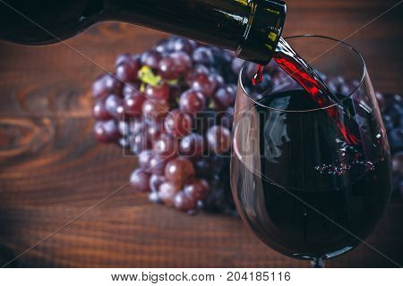 Pouring Red Wine Into The Glass With A Bunch Of Red Grapes Against Wooden Background