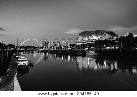 Newcastle upon Tyne UK. Famous Millennium bridge at night. Illuminated landmarks with river Tyne in Newcastle UK. Black and white