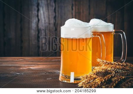 Two Glasses Of Light Beer With Spikelets Of Barley On The Wooden Background. Beautiful Background Of
