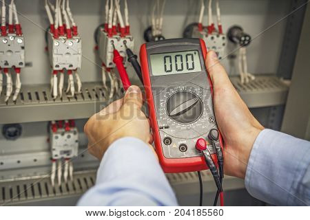 Engineer's hands with multimeter close-up against background of terminal rows of electric automation panel. engineer tests industrial electrical circuits with multimeter in control terminal box.