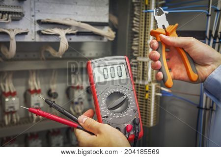 Hands of electrician with multimeter and nippers close-up on background of electric control cabinet for industrial equipment.