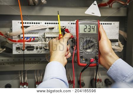multimeter and screwdriver in hands of electrical engineer for automation close-up. Adjustment of industrial control controller. Testing of electrical equipment