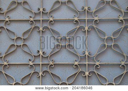 Metalwork pattern on weathered rusty gate. Iron texture geometric background.