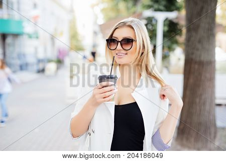 Relaxed Stylish Woman Drinking Coffee Outside On Urban Background