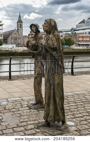 Dublin Ireland - August 7 2017: Great Irish Famine bronze statue set on Custom House Quay along Liffey River in Docklands.. Two figures male and female out of six plus dog total.