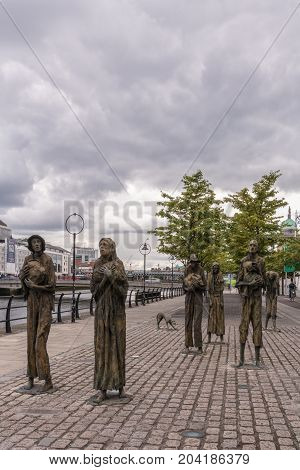 Dublin Ireland - August 7 2017: Great Irish Famine bronze statue set on Custom House Quay along Liffey River in Docklands. All six figures male and female plus dog. Green trees and cloudscape.