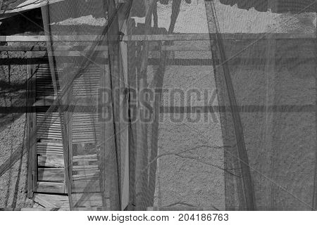 Broken window behind transparent debris netting. Abandoned house black and white.