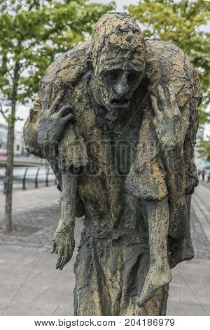 Dublin Ireland - August 7 2017: Great Irish Famine bronze statue set on Custom House Quay along Liffey River in Docklands. One slender male figure carries dead female. Green trees.