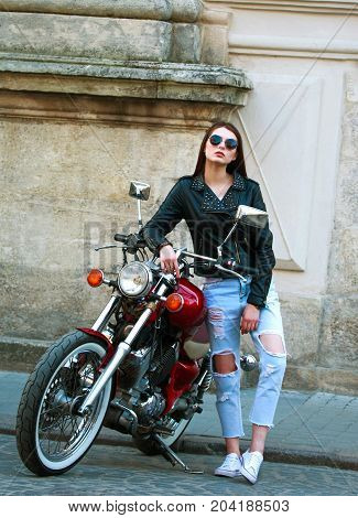 Young stylish woman in a leather jacket on a classic motorcycle in old town