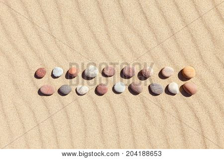 Pattern of colored pebbles on clean sand. The concept of peace and contemplation. Flat lay top view. Zen background harmony and meditation concept