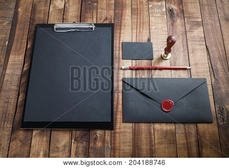 Photo of blank black stationery and corporate identity template on vintage wooden table background. Responsive design template.
