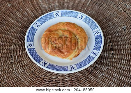 Greek spiral pie traditionally stuffed with cheese leek or spinach. Vegetarian food appetizer dish.