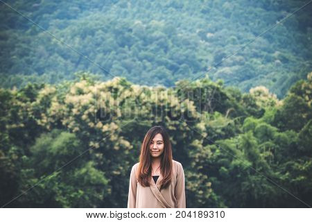 A beautiful Asian woman standing alone with green nature and mountain background