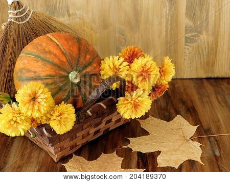 Pumpkin in a wicker basket with flowers, rowan and dry leaves. Autumn still life