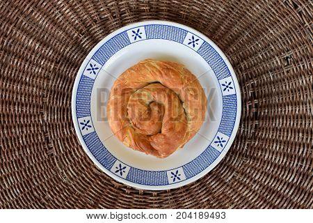 Greek food strifti pita spiral pie filled with feta cheese leek or spinach. Mediterranean cuisine appetizer dish.