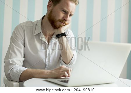 Young Redhair Man Working On Laptop In Room By The Blue Striped Wall