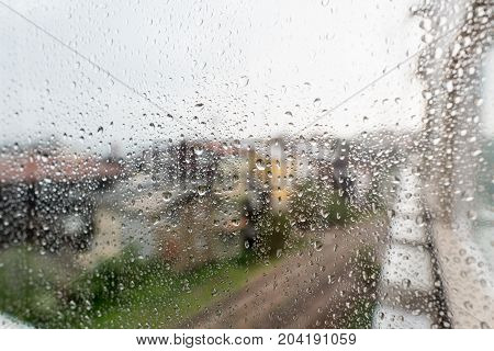 Rain drops on window glasses surface with city background. Natural Pattern of raindrops isolated on urban background.