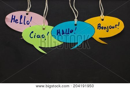 Hello / Speaking Learning Foreign Languages. Colorful Speech Bubbles Hanging From A Cord On Blackboa