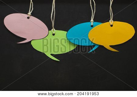 Blank White Speech Bubbles Hanging From A Cord In Front Of A Black Board