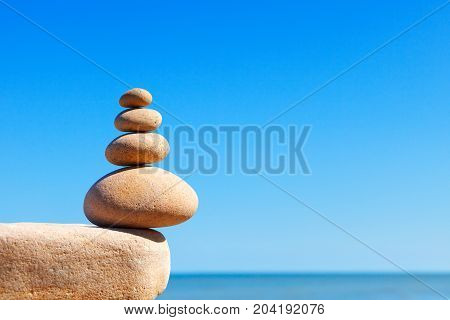 Rock zen pyramid of yellow stones on a background of blue sky and sea. Concept of balance harmony and meditation