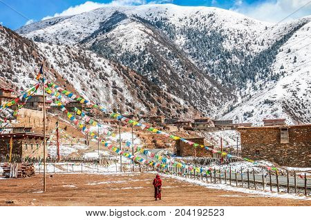 Tibetan Buddhist Monk walking in a beautiful landscape between snow-covered mountains. Shot in Tibet.