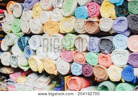 Traditional colorful silk cashmere head scarves or shawls and fabrics composed of a stack background at the bazaar stall in Istanbul Turkey