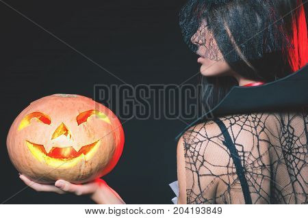 Entrance is limited to nightclub, dress code. Fashion young woman with pumpkin going to Halloween party 2017 Beautiful woman like witch. Moon, scary cemetery. Hallowen costumes, pumpcin