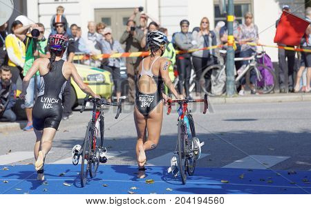 STOCKHOLM - AUG 26 2017: Back of triathlete Deborah Lynch (NZL) and Minami Kubano (JPN) running with cycle in the transition zone in the Women's ITU World Triathlon series event August 26 2017 in Stockholm Sweden