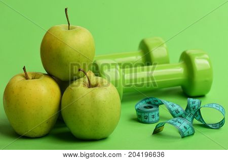 Tape Measure In Cyan Color Near Barbells And Juicy Apples