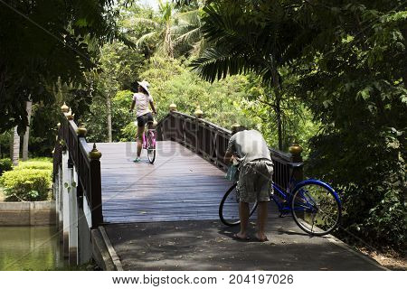 Travelers People Walking And Biking Bicycle In Sri Nakhon Khuean Khan Park And Botanical Garden Or K