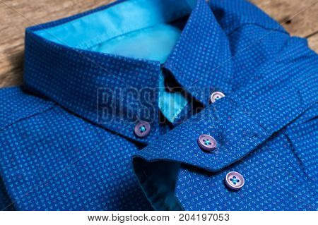 A Blue Men Shirt Is On Wooden Background